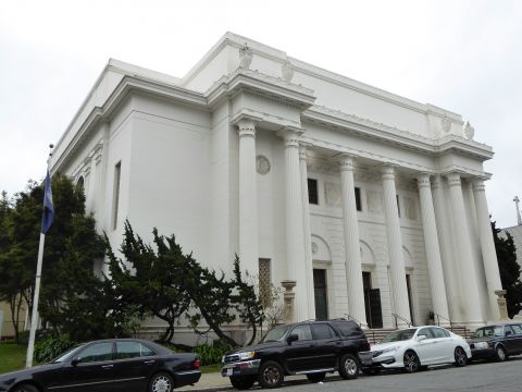 White classical building photographed at an angle with vehicles in front.